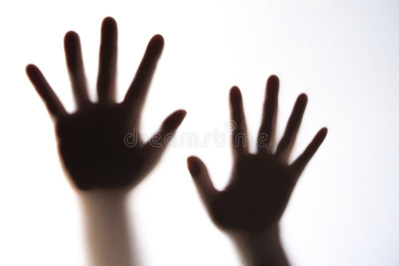 Силуэт руки ` s женщины выражая страх стоковая фотография