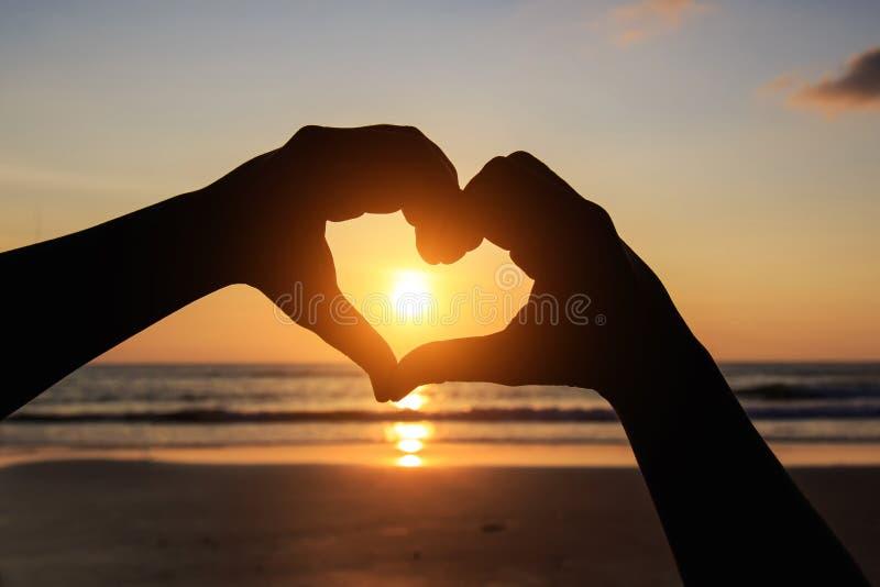 Силуэт рук в символе сердца вокруг солнца стоковое фото