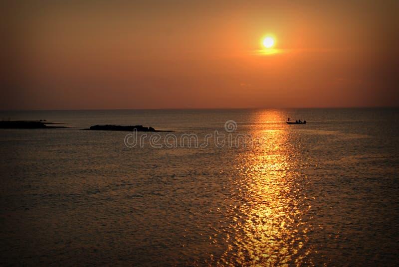 Силуэт рыбной ловли захода солнца стоковое изображение