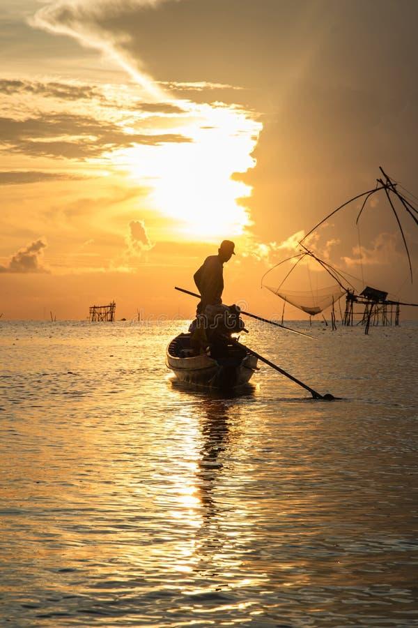 Силуэт рыболова на его шлюпке на восходе солнца в утре стоковые фотографии rf