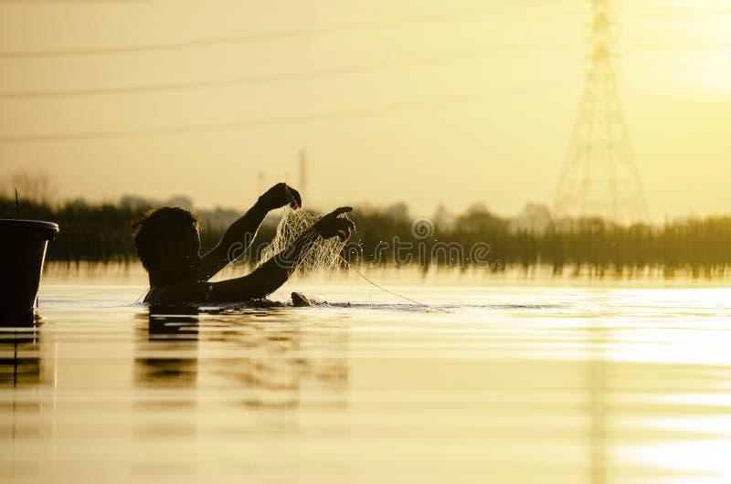 Силуэт рыб рыболова поглощая на большом болоте к югу от Таиланда на утре и высоковольтном поляке предпосылка нерезкости стоковое изображение