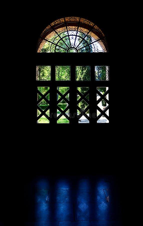 Силуэт сдобренного окна с hudestvennymi выковал решетки с отражениями на каменном поле стоковое фото rf