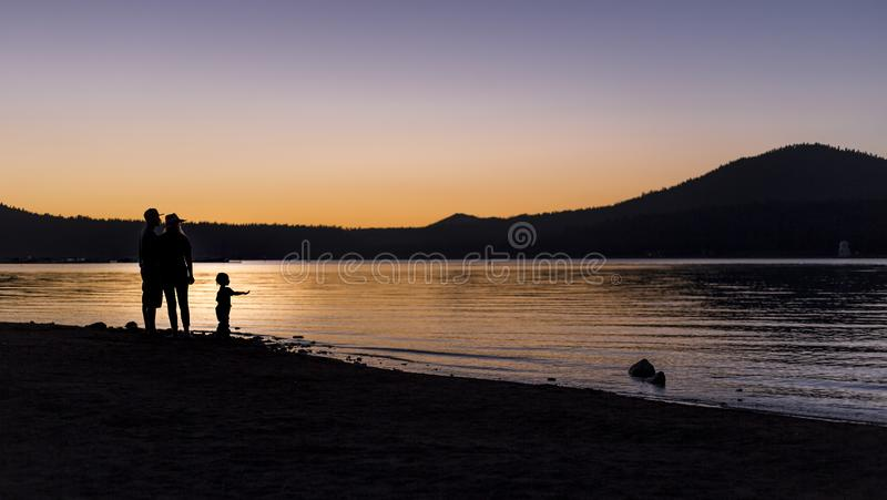 Силуэт семьи на озере стоковое изображение