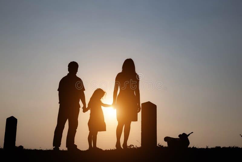 Силуэт семьи состоя из отца, матери и семьи 2 детей счастливой заход солнца Концепция дружелюбного стоковые изображения rf