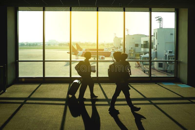 Силуэт семьи с чемоданом идя в аэропорт, человека носит стоковые фото