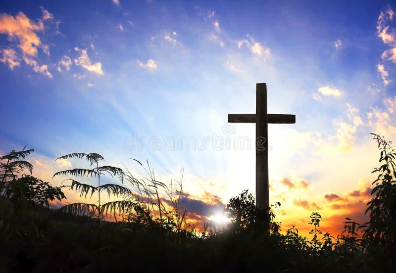 Силуэт символа вероисповедания концепции схематический черный перекрестный в траве над заходом солнца или небом восхода солнца стоковые фотографии rf