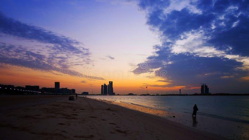Силуэт сиротливой женщины на пляже в шикарном заходе солнца стоковые изображения