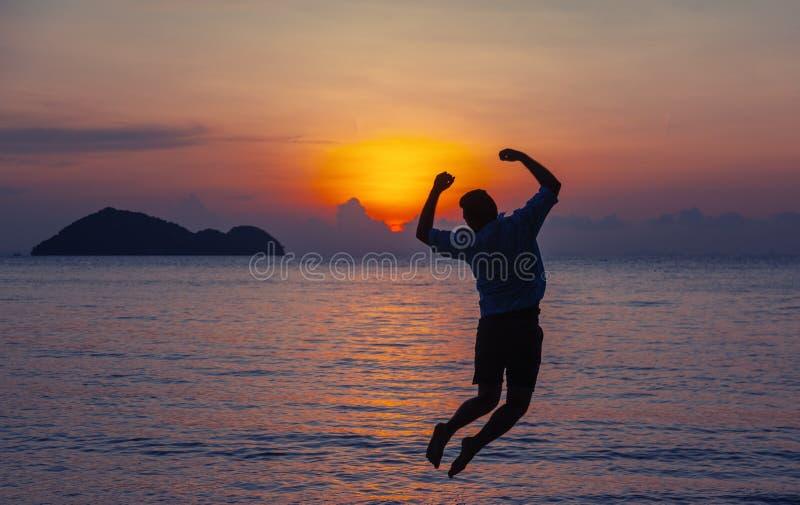 Силуэт скача человека на seashore на концепции захода солнца, человека и природы, перемещении каникул свободы образа жизни красот стоковое фото rf