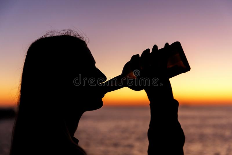 Силуэт спирта девушки выпивая от бутылки на заходе солнца стоковое фото rf