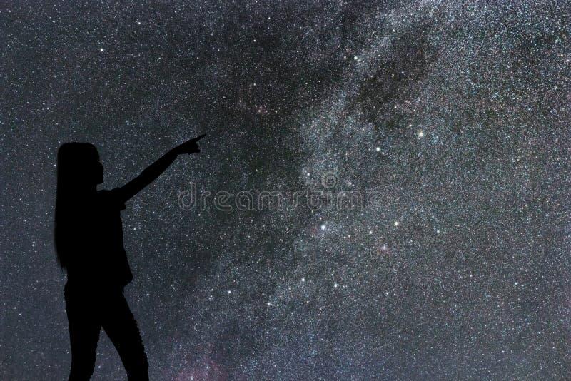 Силуэт стойки женщины самостоятельно в млечном пути и звездах ночи стоковое изображение