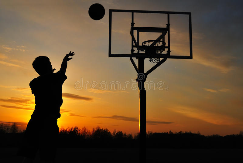 силуэт стрельбы мальчика баскетбола предназначенный для подростков стоковые изображения rf