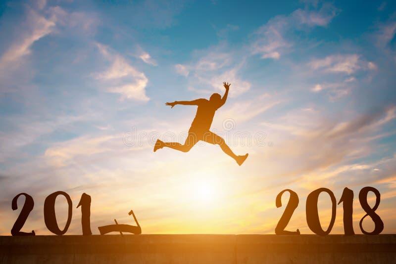 Силуэт счастливого человека скачет между 2017 и 2018 летами в солнцах стоковое фото rf