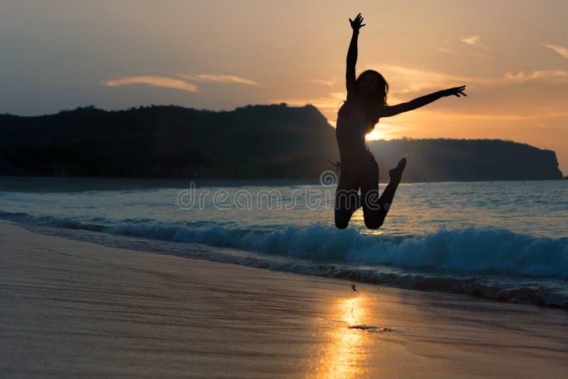Силуэт счастливой радостной женщины скача и имея потеха на пляже против захода солнца Концепция каникул свободы и отдыха стоковое фото rf