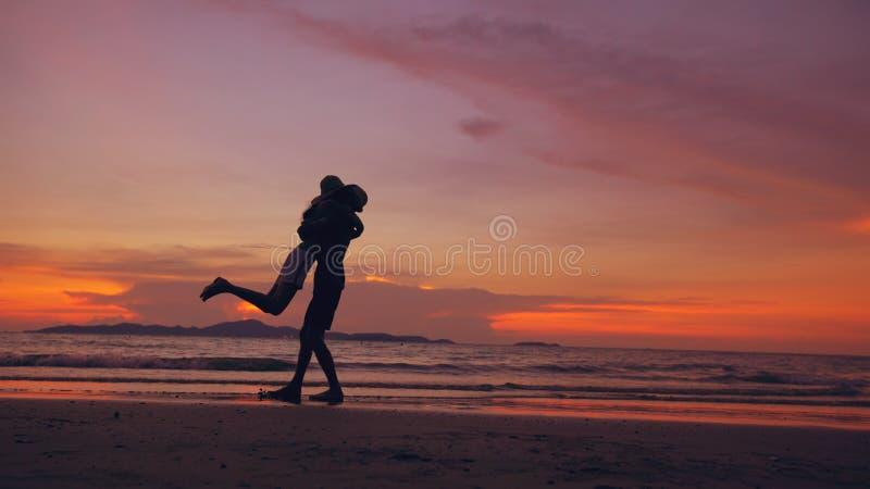 Силуэт счастливых любящих пар встречает и играет на пляже на заходе солнца в береге океана стоковое фото rf
