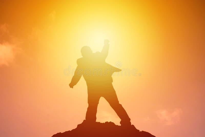 Силуэт счастья успеха торжества бизнесмена на верхней части горы Дело, достижение, успех, концепция стоковая фотография rf