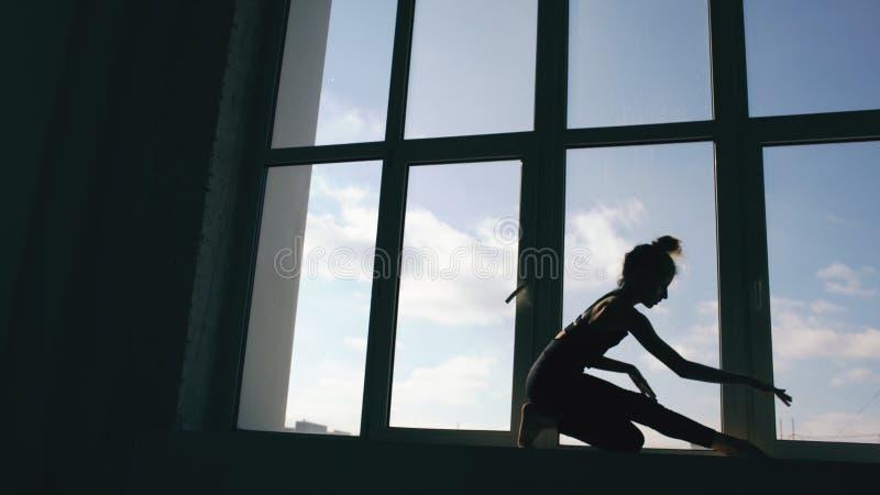 Силуэт танца представления танцора маленькой девочки современного на windowsiil в студии танца внутри помещения стоковое изображение rf