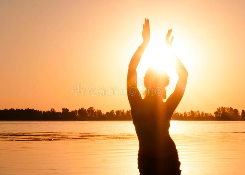 Силуэт тонкой женщины танцуя традиционный племенной танец живота на пляже на восходе солнца стоковые изображения