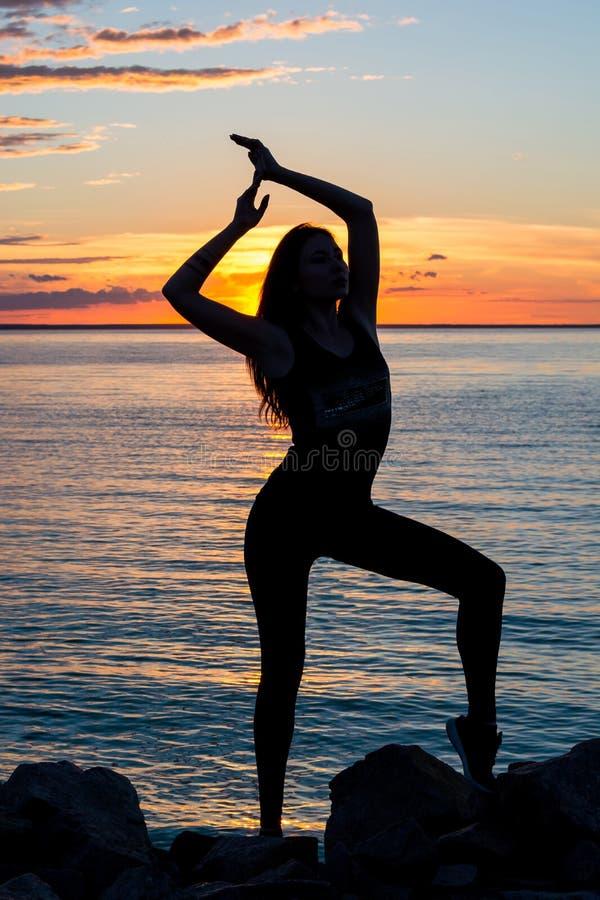 Силуэт худенькой женщины, которая кто делает йогу перед стоковое фото rf