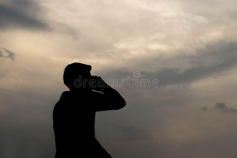 Силуэт человека говоря на смартфоне стоковое изображение rf
