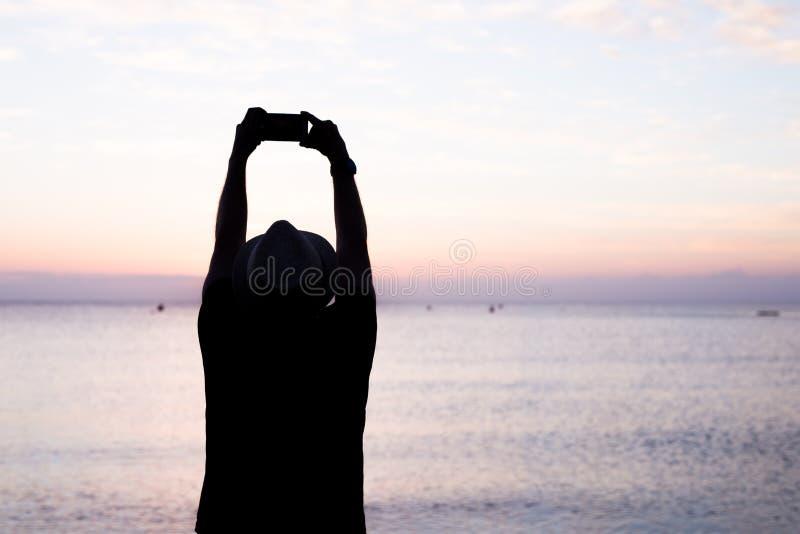 Силуэт человека держа мобильный телефон фотографируя снаружи во время восхода солнца или захода солнца на пляже Черное светлое фо стоковые изображения rf