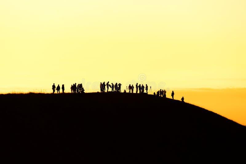 Силуэт человека задерживает руки на пике горы, концепции успеха стоковое фото