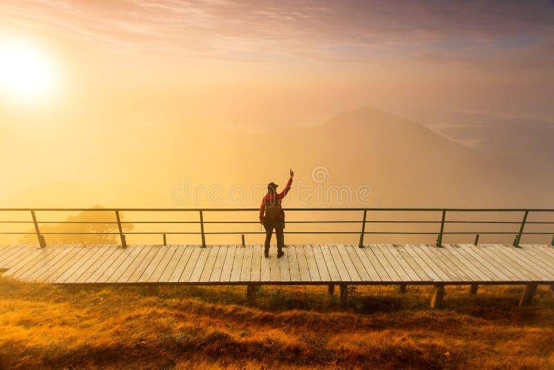 Силуэт человека задерживает руки на пике горы, концепции успеха стоковое фото rf