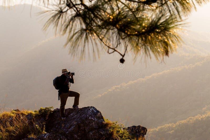 Силуэт человека задерживает руки на пике горы, концепции успеха стоковое изображение rf