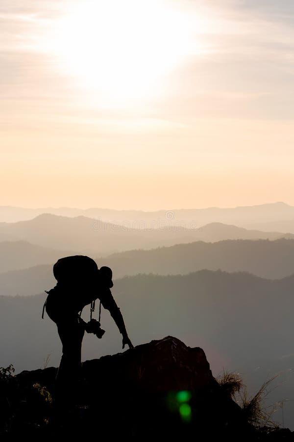 Силуэт человека задерживает руки на пике горы, концепции успеха стоковые изображения