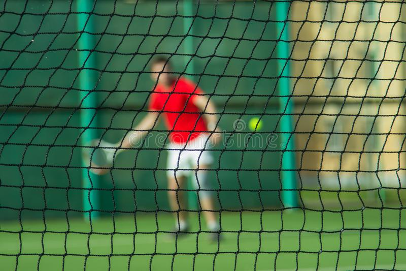 Силуэт человека за сетью тенниса стоковая фотография