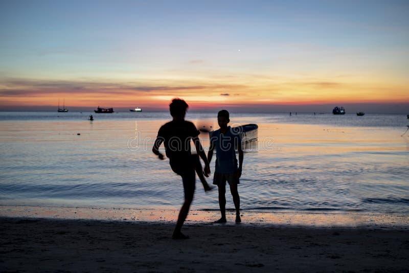 Силуэт человека 2 играя футбол на пляже моря против солнец стоковое изображение