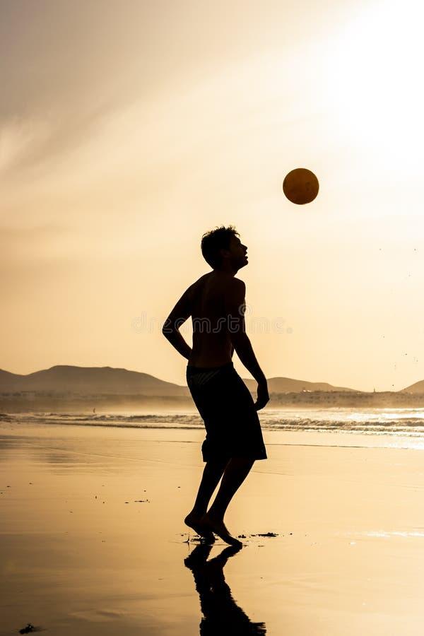 Силуэт человека играя футбол футбола на заходе солнца Пляж Famara, Лансароте, Канарские острова, Испания стоковое фото