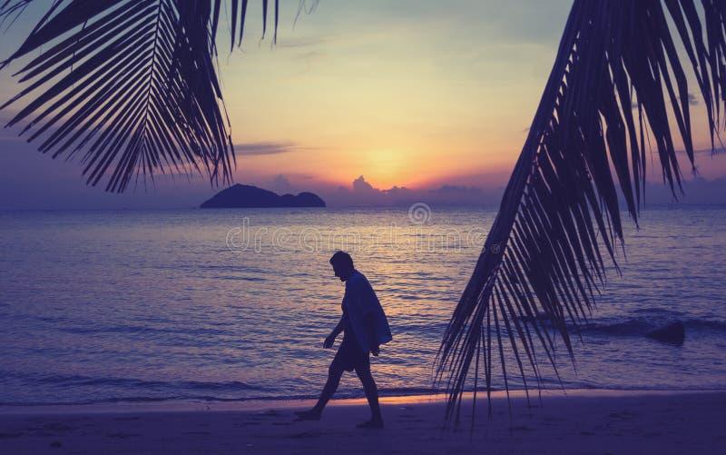 Силуэт человека идя вдоль seashore на концепции захода солнца, человека и природы, каникулах каникул свободы образа жизни красоты стоковая фотография