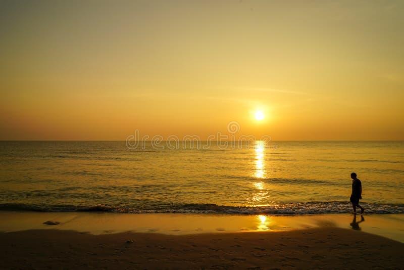 Силуэт человека идя barefoot на пляж песка на сцене восхода солнца утра с видом на море, отражением воды волны стоковые изображения rf
