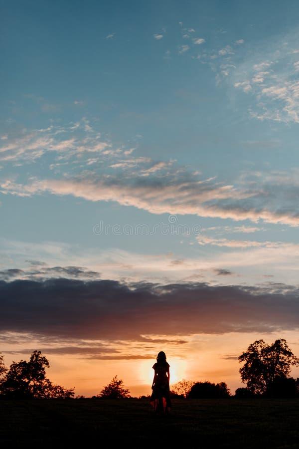 Силуэт человека на заходе солнца стоковое фото rf
