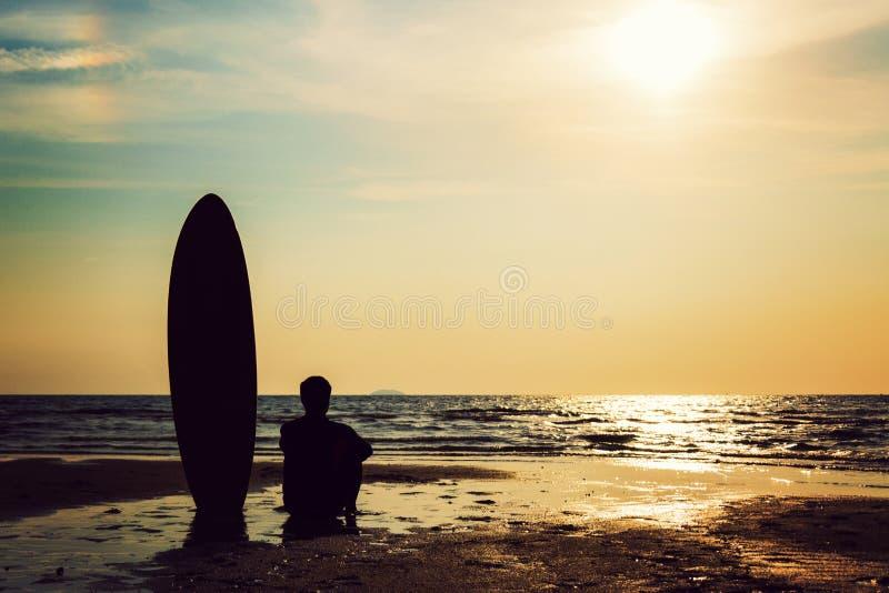 Силуэт человека прибоя сидя с surfboard на seashore стоковая фотография rf