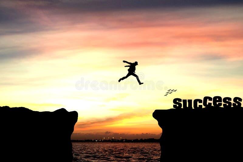 Силуэт человека скача над скалой стоковое изображение rf