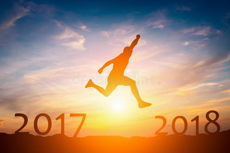 Силуэт человека скачет от концепция 2017 до 2018 успеха в солнце стоковые изображения rf