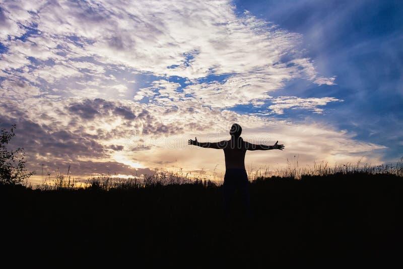 Силуэт человека стоя в полях при оружия протягиванные для того чтобы встретить солнце стоковые изображения rf