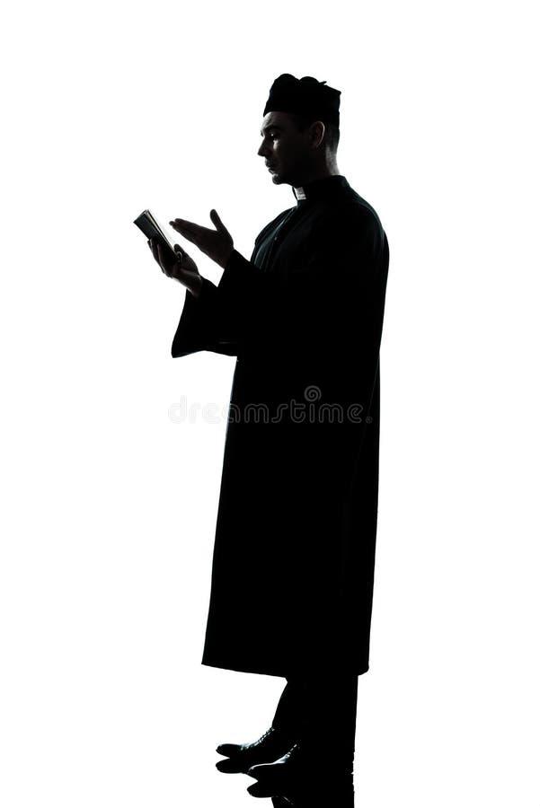 силуэт чтения священника человека библии стоковые изображения