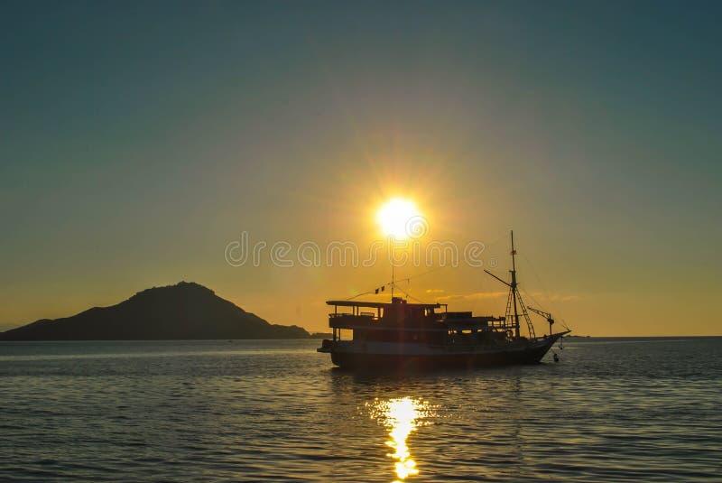 Силуэт шлюпок в море на заходе солнца Красивый заход солнца в тропическом острове Komodo, Labuan Bajo, передних частях, Индонезии стоковые изображения rf