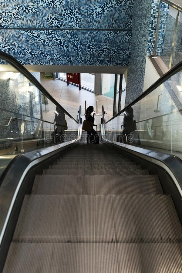 Силуэт эскалаторов аэропорта девушки взбираясь с чемоданом стоковые изображения rf