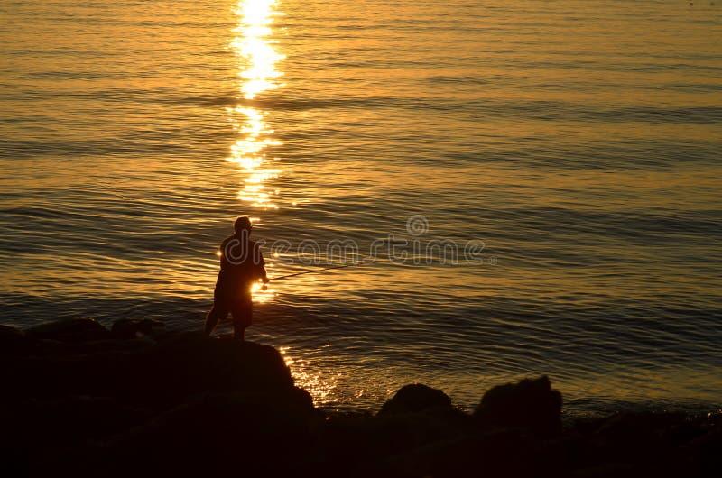 Силуэт fisher на скале моря на восходе солнца стоковое фото