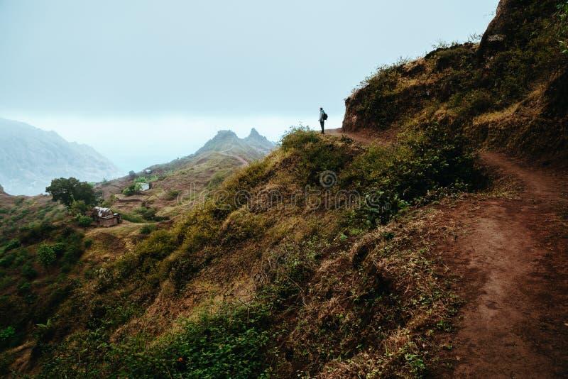 Силуэт Hiker смотрит в долину и слушает к безмолвию Туман и туман висят над горными пиками на стоковое фото