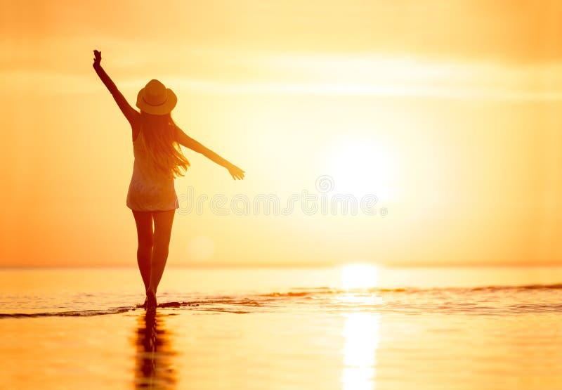 Силуэт ` s дамы с поднятым пляжем захода солнца оружий стоковые изображения rf