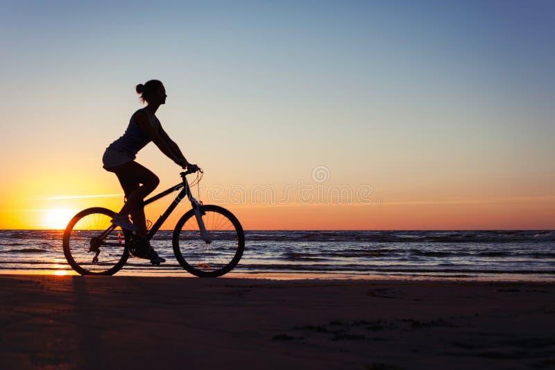 Силуэт sporty велосипеда катания женщины на пестротканой предпосылке захода солнца стоковые изображения rf