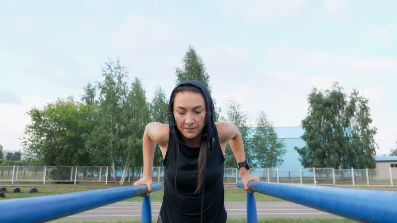 Сильная девушка в sportswear делая трицепс работает внешнее стоковые фото