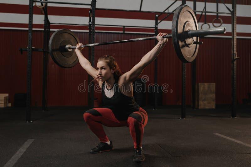 Сильная женщина спорт делая сидения на корточках с тяжелыми накладными расходами штанги на спортзале crossfit стоковое фото rf