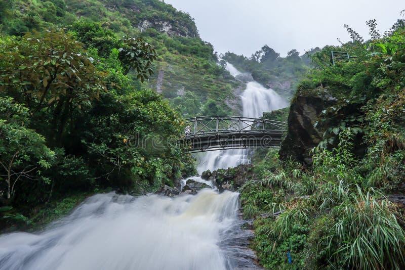 Сильная подача воды и стал-сдобренный мост на серебряном водопаде Bac Thac водопада в Sapa, провинции Lao Cai, северном Вьетнаме стоковое изображение rf
