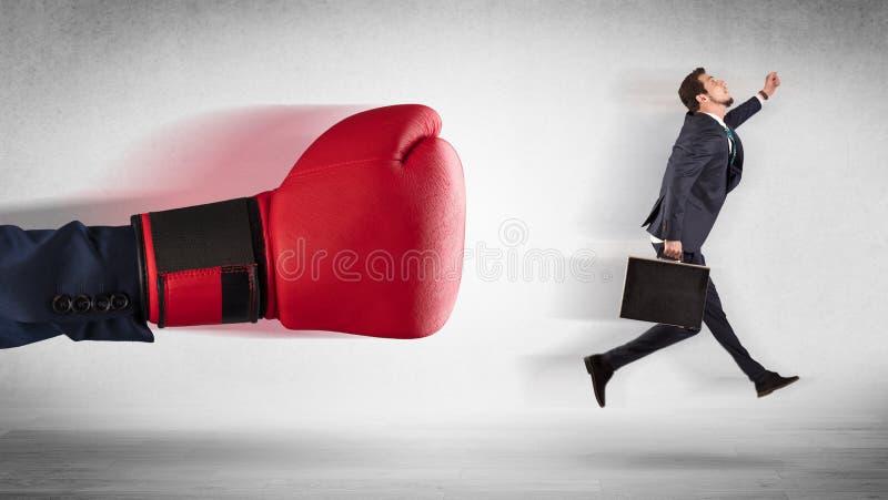 Сильная рука кладя маленького бизнесмена в коробку стоковые изображения rf