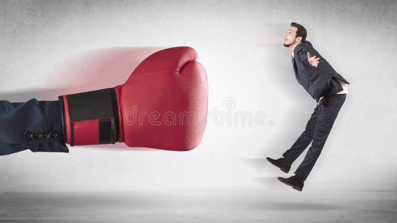 Сильная рука кладя маленького бизнесмена в коробку стоковое фото